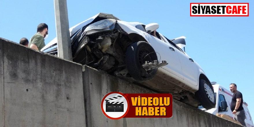 Kaza yapan otomobil yolun ortasındaki duvarda asılı kaldı